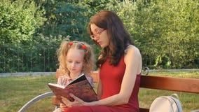 Weinig Leuke Dochter die met Twee Paardestaarten Boek met Haar Moeder die in Oogglazen lezen op de Bank in het Park zitten stock videobeelden