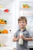 Weinig leuke fles van de jongensholding melk dichtbij open Royalty-vrije Stock Afbeeldingen