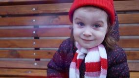 Weinig leuke het glimlachen meisjeszitting op de bank in het stadspark in de wintertijd stock video