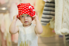 Weinig leuke 3 jaar meisjes in een rode hoedenstip bij de opslag van kinderenkleren Royalty-vrije Stock Foto's