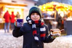 Weinig leuke jong geitjejongen die Duitse worst eten en hete kinderen drinken slaat op Kerstmismarkt Gelukkig kind  royalty-vrije stock afbeeldingen