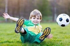 Weinig leuke jong geitjejongen van speelvoetbal 4 met voetbal op gebied, in openlucht Stock Foto's