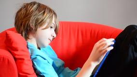 Weinig leuke jongen die een boek op de leunstoel lezen stock videobeelden