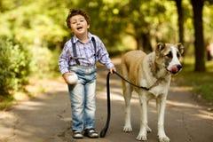 Weinig leuke jongen die met zijn hond speelt Royalty-vrije Stock Afbeelding
