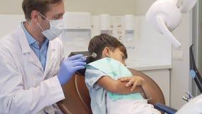 Weinig leuke jongen die tonend zijn tanden aan de tandarts, die droevig en doen schrikken kijken weigeren stock videobeelden