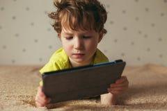 Weinig leuke jongen in een groene T-shirt speelspelen op een tablet en het letten op beeldverhalen Peuter met tablet stock afbeelding