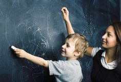 Weinig leuke jongen in glazen met jonge echte leraar, klaslokaal die bij kido van de bordschool bestuderen royalty-vrije stock foto's