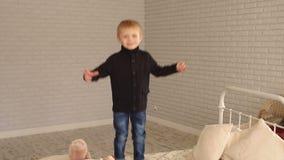 Weinig leuke jongen in jeans en sweater die op het bed thuis springen stock footage