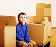 Weinig leuke jongen in lege ruimte met vele dozen, remoove aan nieuw huis stock afbeelding