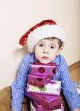 Weinig leuke jongen met Kerstmisgiften thuis sluit omhoog emotioneel gezicht op dozen in santas rode hoed Stock Fotografie