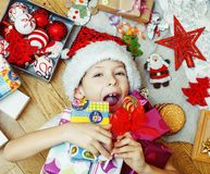 Weinig leuke jongen met Kerstmisgiften thuis sluit omhoog het emotionele gelukkige glimlachen binnen knoeien met speelgoed, leven royalty-vrije stock foto