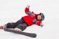 Weinig leuke jongen met skis en een skiuitrusting Weinig skiër in royalty-vrije stock fotografie