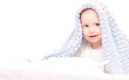 Weinig leuke jongen onder deken op het bed stock foto