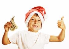 Weinig leuke jongen in santas rode die hoed met contant geld Amerikaan wordt geïsoleerd  Royalty-vrije Stock Foto's