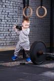 Weinig leuke jongen in sportwear status met schijf van barbell bij de gymnastiek en het kijken op barbell stock afbeelding