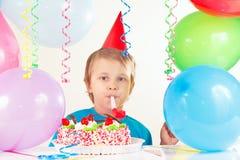 Weinig leuke jongen in vakantiehoed met verjaardagscake met fluitje en feestelijke ballons Royalty-vrije Stock Fotografie