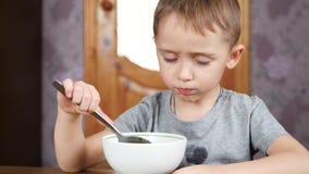 Weinig leuke jongen zit bij de lijst en eet soep met eetlust Gezonde voeding van kinderen stock video