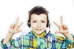 Weinig leuke Kaukasische jongen in hoofdtelefoons die het gelukkige glimlachen stellen geïsoleerd op witte achtergrond, het conce stock foto
