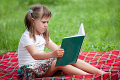 Weinig leuke meisjeskleuter met boek in park Stock Fotografie