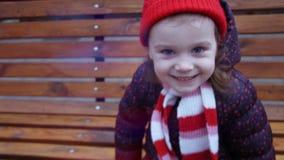 Weinig leuke meisjeszitting op de bank in het stadspark in de wintertijd en het lachen stock video