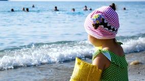 Weinig leuke meisjeszitting op het strand en werpt kiezelstenen in het water stock videobeelden