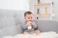 Weinig leuke zitting van het babymeisje in ruimte bij bankconsumptiemelk van fles en het glimlachen Gelukkige zuigeling Het binne royalty-vrije stock afbeeldingen