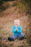 Weinig manierjongen in een bos die blauwe sweater dragen en jeanse Stock Fotografie