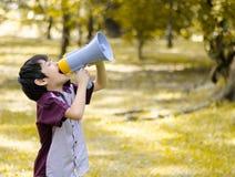 Weinig megafoon die van de jongensgreep in het park schreeuwen Stock Foto