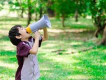 Weinig megafoon die van de jongensgreep in het park schreeuwen Stock Fotografie