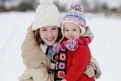 Weinig meisje van de de winterbaby en haar jonge moeder Stock Afbeelding