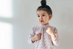 Weinig meisje van de kindbaby met haar haar verzamelde zich in een broodje dat op bovenkant en verbolgen door de onrechtvaardighe royalty-vrije stock fotografie