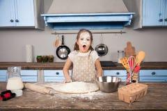 Weinig meisje van de kinddochter helpt haar moeder in de keuken om bakkerij, koekjes te maken Zij heeft overal een vloed haar royalty-vrije stock foto