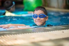 Weinig mengelings Aziatische Arabische jongen die bij zwembad openluchtactiviteit zwemmen stock foto's