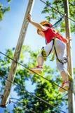 Weinig moedig Kaukasisch meisje die bij openluchttreetop avonturenpark beklimmen royalty-vrije stock afbeelding
