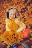 Weinig mooi blond meisje met grote pompoen op de herfstachtergrond stock foto's