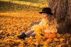 Weinig mooi blond meisje met grote pompoen op de herfstachtergrond royalty-vrije stock afbeeldingen