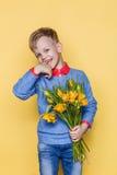 Weinig mooi kind met een boeket van tulpen De zoon geeft mammabloemen op Vrouwen` s Dag, Moeder` s Dag Verjaardag De dag van de v Stock Fotografie