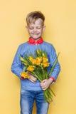Weinig mooi kind met een boeket van tulpen De zoon geeft mammabloemen op Vrouwen` s Dag, Moeder` s Dag Verjaardag De dag van de v Stock Foto's