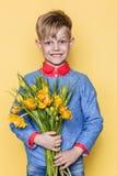 Weinig mooi kind met een boeket van tulpen De zoon geeft mammabloemen op Vrouwen` s Dag, Moeder` s Dag Verjaardag De dag van de v Stock Afbeeldingen