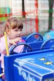 Weinig mooi meisje berijdt op heldere auto in pretpark stock fotografie