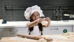Weinig mooi meisje in chef-kokhoed en schort Het concept van de jong geitjechef-kok Het aanbiddelijke meisje spelen met deeg 4K stock footage