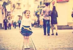 Weinig mooi meisje die op de stadsstraat lopen stock afbeelding