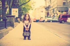 Weinig mooi meisje die op de stadsstraat lopen stock foto's