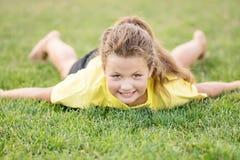 Weinig mooi meisje die yogaasana maken liggend op groen gras Fietser of fietser het berijden langs een concreet fietspad Stock Afbeelding