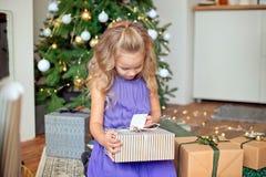 Weinig mooi meisje met blond krullend haar overweegt haar giften tegen de achtergrond van de Kerstboom Kerstmis royalty-vrije stock fotografie