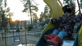 Weinig mooi meisje naast haar moeder in een kleurrijk jasje beklimt een heuvel in het de lentepark met lange pijnbomen bij zonson stock footage