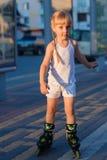 Weinig mooi meisje op rolschaatsen bij een park Royalty-vrije Stock Fotografie