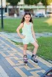 Weinig mooi meisje op rolschaatsen bij een park Stock Fotografie