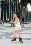 Weinig mooi meisje op rolschaatsen bij een park Stock Foto's