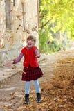 Weinig mooi meisje in vest werpt op bladeren stock fotografie